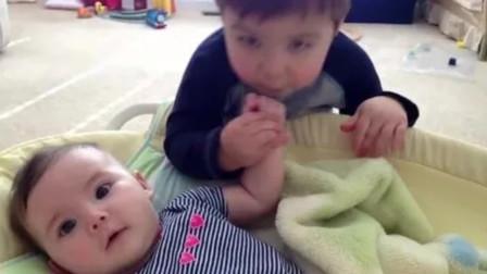 小哥哥给摇篮里的妹妹唱歌,还不忘时不时亲一下小宝宝,太暖了!