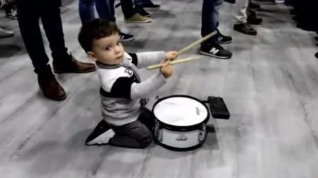 小宝宝跟着大人玩敲鼓,坐在一旁显得好小一只,画面感太好玩了!