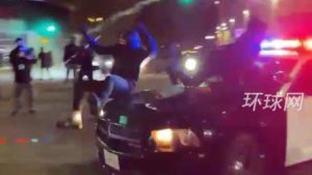 美国2名者爬上警车砸引擎盖,警车突然加速,一人被车顶走
