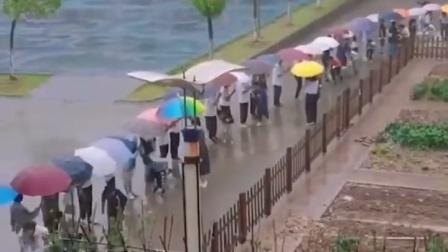 """小学生被暴雨困住,师哥师姐拼成""""爱心伞桥""""送学弟学妹返回"""