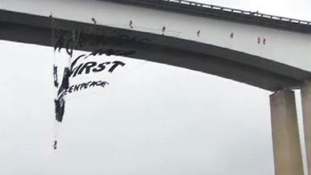行动人员悬空身体展横幅,呼吁重视气候和民众