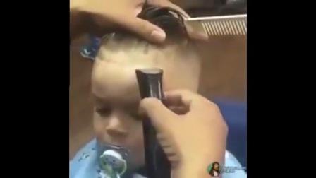 一个剪头发的小男孩,嘴里叼着奶嘴,很酷很淡定。