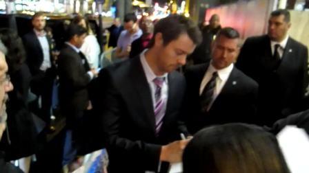 signs autographs at premiere