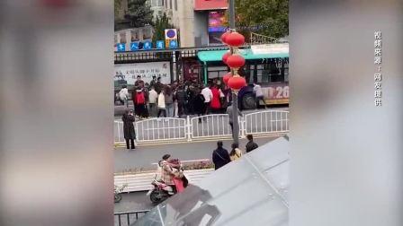 公交车冲向站台两人被压 几十位市民推车救人