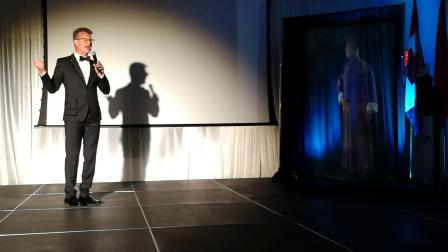 """2019年9月15日晚,加拿大著名学者、笑星、主持人大山借助全息影像技术与""""另一个自己""""合说传统相声《蛤蟆鼓》。地点:多伦多国际电影节总部。"""