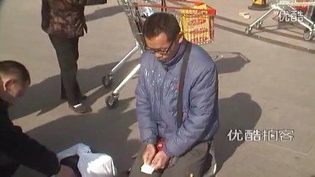 """【拍客】男子抱""""妻子""""骨灰盒乞讨500元路费 两次被群众识破"""