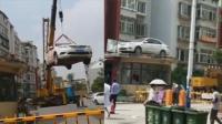 女司机开车堵小区门 车被吊到房顶