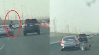 男子高速路探身打司机 摔下车险被压