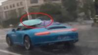 一司机冒雨撑伞驾驶保时捷911敞篷跑车行驶 真是让人瞠目结舌
