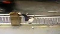 尴尬!女子横穿马路翻栏杆 跌倒头部被卡