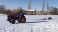 真会玩!男子开拖拉机拉3娃滑雪