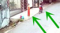 红衣女子站在路边玩手机, 旁边经过一辆摩托车, 监控拍下不耻一幕!