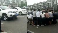 江苏一女子被卷车底 危急时刻众路人抬车救援