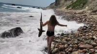 暖心一幕! 小鲨鱼被困海滩 15岁小美女徒手将其抓起放归大海