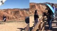 女游客翻越护栏 脚踩丹霞地貌拍照