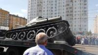 俄一阅兵坦克驶上运输车时侧翻冒烟