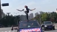 实拍男子车顶单腿站立表演平衡术
