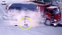 惊险! 男子骑电动车听音乐 横穿马路遭两货车夹击 两回死里逃生
