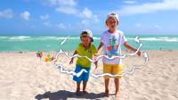 熊孩子们通过一面镜子穿越到了沙滩, 两个小家伙玩的好开心呀! 真是有趣啊!