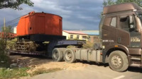重型卡车拉着一台重型履带式打夯机, 差一点卡在了路基上