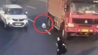 面包车转弯时婴儿突然滚落 险遭身后渣土车碾压
