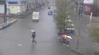 感动!开学日遇暴雨 两名路人轮流抱孩子过积水