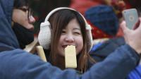 女游客在印度街头买冰棍吃,刚要放进嘴里,导游见状大喊停下