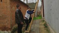 农村小伙换电线不敢爬梯子,让电工帮忙扶着,被电工熊几句老实了