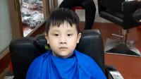 理发师给乖乖理发的男孩剪个瓜子头,大家都夸帅气