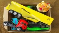 户外草丛下盖着一箱恐龙、卡车、犀牛玩具