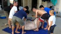 泰国人吃牛肉真豪气,一整头牛塞进铁桶里煮,七八个小伙才抬得动