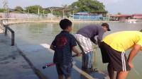 小孩跟爸爸钓鱼,上钩的鱼他越拉越过瘾,爸爸在旁边等得心急!