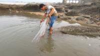 阿雄用渔网围着水坑做了个陷阱,撒上诱饵,就等着退潮后来抓大货