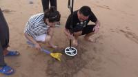 拿着金属探测器在海滩探宝,挖出的东西引一群人围观