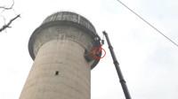 高难度!印度一头牛爬上60多米高水塔 被吊车救下
