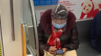 硬核防疫!大妈用塑料油桶自制防护罩坐地铁