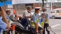 老人不配合执法阻碍交通 交警用铁棍穿过车轮连人带车抬走