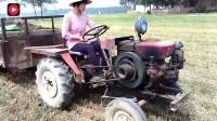 这可不是作秀,农村妇女实打实地摇着挂四根皮带的拖拉机,开上就走