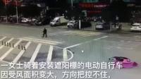 险!大风吹翻电动车,两位热心市民看到后将其扶起。提醒:摩托车、电动车请勿安装遮阳棚!