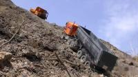 挖掘机越过泥泞路卡车在泥、水和砾石中工作